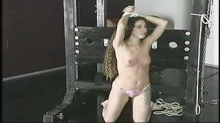 lean a-cup bdsm brunette with arms roped overhead stands submissively Thumb
