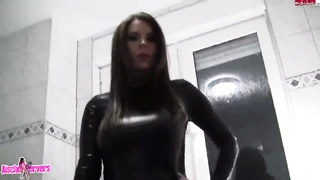 Deviance street walker in latex suite showing off her soaked cellphone Thumb